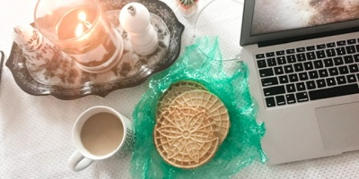 Image shows a laptop with tea and biscuits