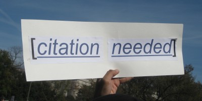 "Image shows a sign held up against a blue sky, above a crowd. Sign reads ""citation needed""."