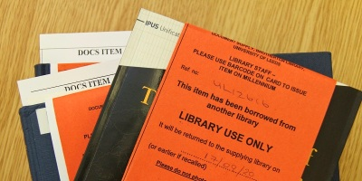 A pile of books with a label saying borrowed from anothre library
