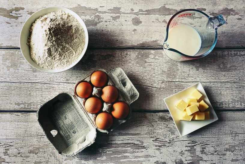Eggs, flour, butter and milk on a wooden table, viewed from above.