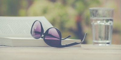 Image shows a pair of sunglasses resting on an open book