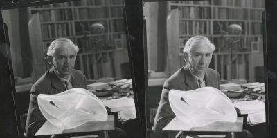 A scanned image of two old black and white photographs of Herbert Read sat behind a white sculpture by Naum Gabo. Herbert Read is sat in a wool suit in his office at his house, there is a wall of bookshelves behind him. He is staring straight in to the camera in both shots, the angle of his only slightly different in each one. On the desk next to him are strewn sheets of papers and several books laid open.