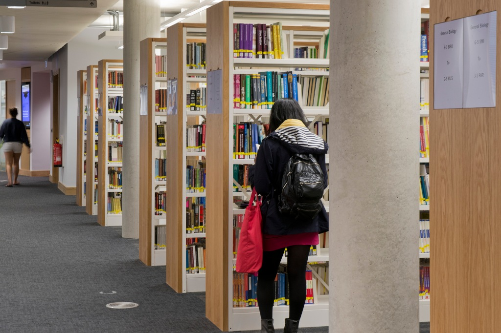 A student searches the shelves in the Library